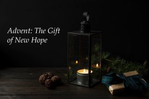 A tabletop display of a lantern with a lighted candle, pine cones and a pine branch, and a gift wrapped in brown paper and a Blackwatch plaid bow