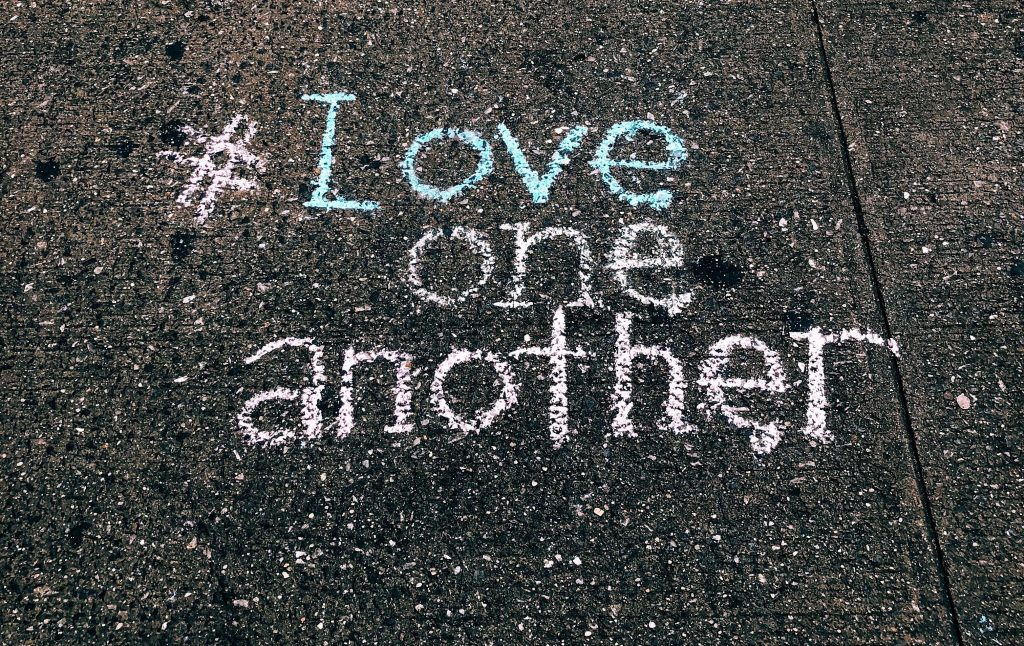 """Hashtag Love One Another"" written in sidewalk chalk on pavement"
