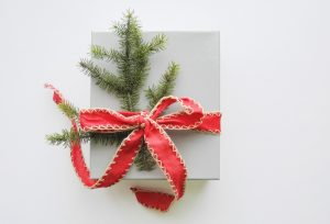 A box wrapped in white paper with a simple red ribbon bow and a sprig of evergreen